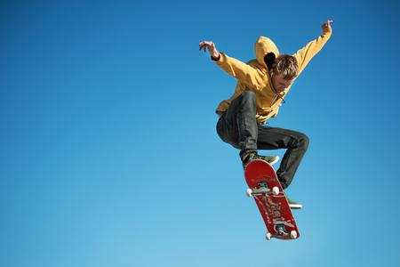 Een tiener skateboarder doet een ollie trick op achtergrond van blauwe hemel gradiënt Stockfoto