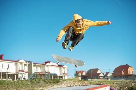 A teenager skateboarder does an flip trick in a skatepark on the outskirts of the city Stok Fotoğraf