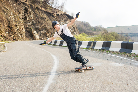 Longboarder on longboard in overalls helmet and gloves performs a stand-up slide at speed while on a mountain road serpentine in the mountains against the backdrop of a beautiful mountain landscape