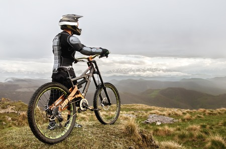 freeride: The rider in the full-face helmet and full protective equipment on the mtb bike stands on a rock against the background of a ridge and low clouds
