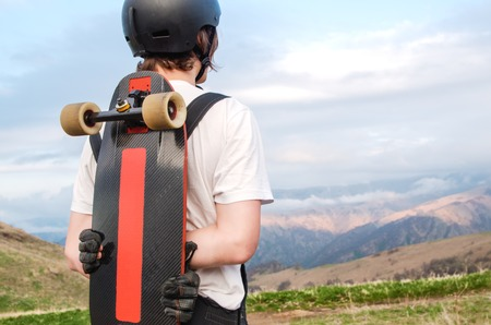 steep: A young man in a helmet wearing gloves with a board in his hands and dressed in a combo stands on a precipice high in the mountains against the backdrop of the setting sunset