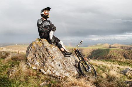 A professional downhill rider sits on a stone resting after a tense race on a mtb bike