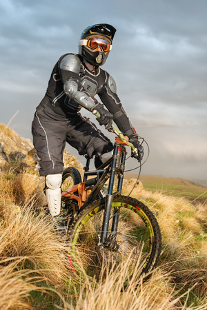 road bike: Downhill rider on a mountain bike in a mountain bike rides along the road in nature against the backdrop of the mountain range of mountains and rainy skiesExtreme Sport Concept.