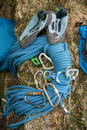 Used equipment for climbing where the rope carbines and climbing slippers lie on a rock