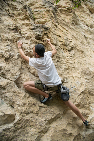 magnesia: A young man is engaged in rock climbing on a steep rock