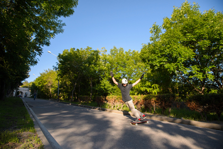A young guy action makes a stand-up slide on a longboard in the resort area of the city