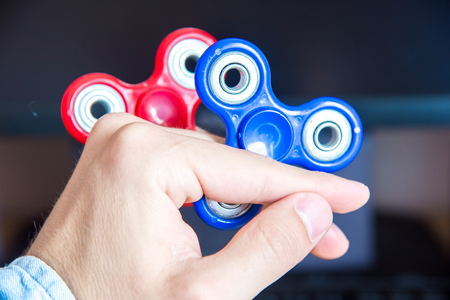 Mans hand holds two multi-colored spinners on the background of a personal computer close-up Stock Photo