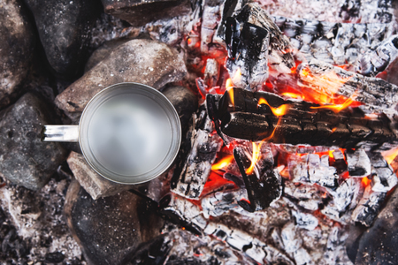 Close-up view from above with a mug of water standing in a fire on the coals and heated