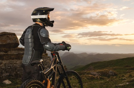 The rider in full protective equipment on the mtb bike is riding toward the sunset in the rays of the sunset sun against the background of the rocks of the setting sun and clouds