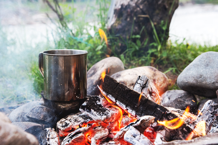 The boiling liquid in a stainless mug stands on the stones in the fire