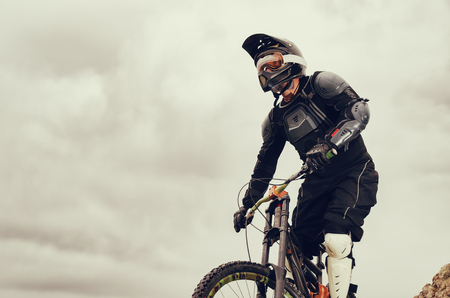 Downhill rider on a mountain bike in a mountain bike rides along the road in nature against the backdrop of the mountain range of mountains and rainy skiesExtreme Sport Concept.