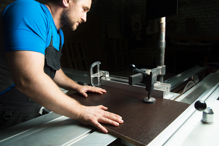 The master prepares the workpiece for cutting on a circular machine