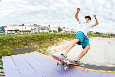 Teenager skater in a cap and shorts on rails on a skateboard in a skate park