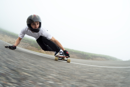 A young guy in a full face helmet in a slide passes a turn Stock Photo