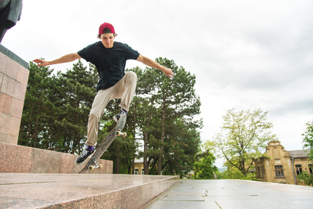 Long-haired skater-teenager in a T-shirt and a sneaker hat jumps an alley against a stormy sky Stockfoto