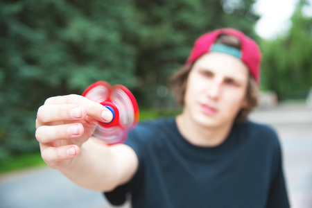 A long-haired hipster in a cap sits on a bench and spins a fidget-spinner
