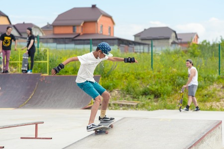 Skateboarding contest in skate park of Pyatigorsk.Young Caucasian skateboarders riding in outdoor concrete skatepark.Skaters compete for prize..Young skater boys ready to roll in on skate ramp