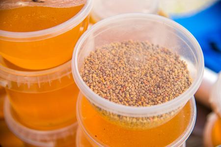 Bee pollen granules in a plastic jar standing on jars of honey