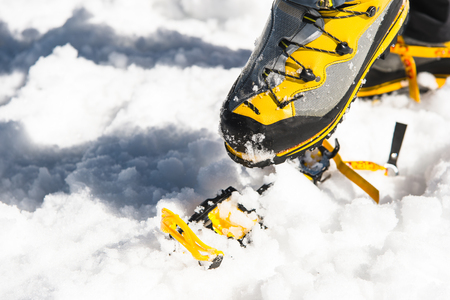 traction: A young guy hiker dresses climbing Crampons over mountaineering shoes For walking through Glacier
