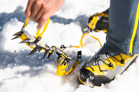 crampon: A young guy hiker dresses climbing Crampons over mountaineering shoes For walking through Glacier