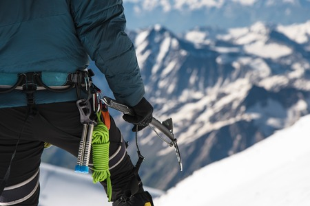 Close up A young guy climber holds in his hand an ice-ax standing on a summit high in the mountains. Extreme sport concept