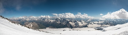 Panorama of the Caucasian ridge with clouds hanging on tops of mountains