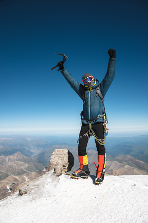 Professional guide Hiker at the top of the rock with his hands up is pleased with the next victory of the ascent