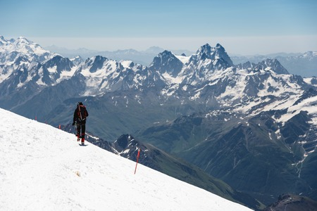 Mountaineer in the mountains strolls along the snowy slope against the background of snow-capped peaks and horizon Фото со стока