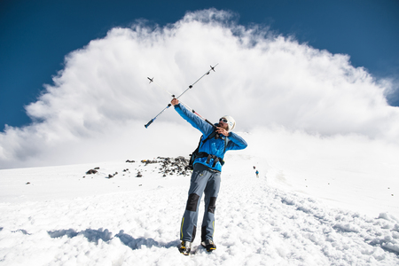 eminence: Backpacker in the mountains pretends to shoot arrows on the example of sticks for Nordic walking Stock Photo