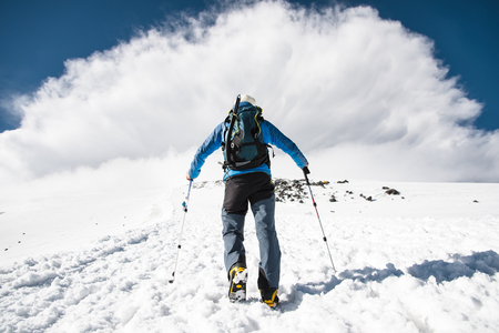 Mountaineer rises uphill to meet a mountain storm coming from the mountain
