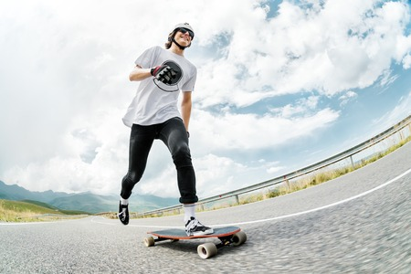 A guy in a helmet and sunglasses accelerates pushing his foot on his longboard