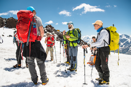 A team of climbers led by a guide discusses the upcoming ascent Stock Photo