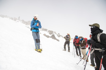 crampon: A team of climbers led by a guide discusses the upcoming ascent Stock Photo