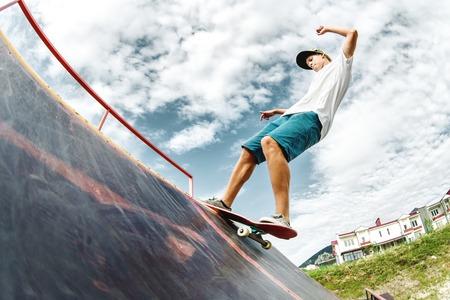 El patinador adolescente cuelga sobre una rampa en una patineta en un parque de patinaje Foto de archivo - 84789384
