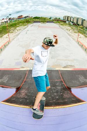 Patinador adolescente se cuelga sobre una rampa en un monopatín en un parque del patín Foto de archivo - 84789385