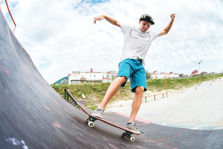 Teen skater rides over a ramp on a skateboard in a skate park