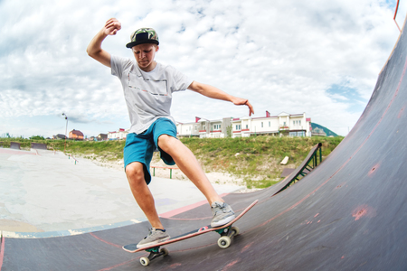 Teen skater rides over a ramp on a skateboard in a skate park Stok Fotoğraf - 84789408