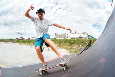 Tiener skater rijdt over een helling op een skateboard in een skatepark