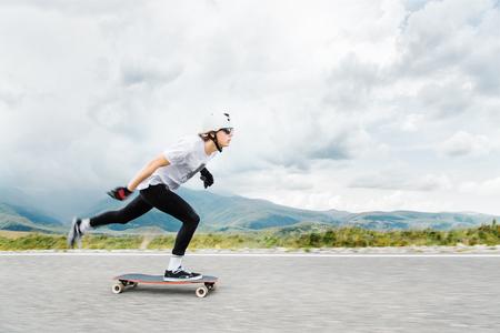 젊은 Longboarder 그의 시골 길을 그의 longboard에 그의 발을 푸시합니다. 스톡 콘텐츠 - 84796522