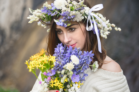 waterfall model: Portrait of a girl with a wreath on her head and a bouquet of flowers in her hands against a waterfall Stock Photo