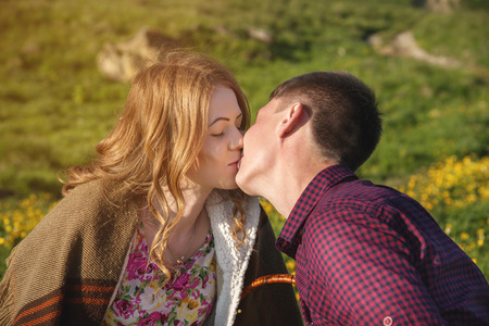young couple kissing on a background of a landscape close-up