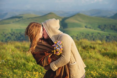 Young happy couple kissing on nature against the beautiful Caucasian landscape.