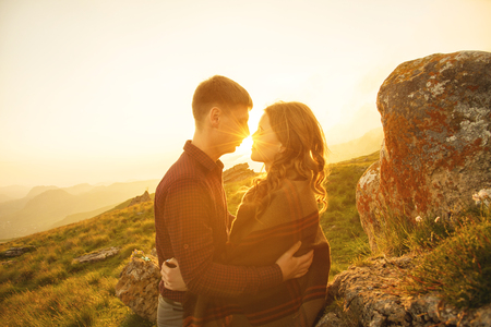 Young happy couple kissing in nature against the setting sun at sunset.