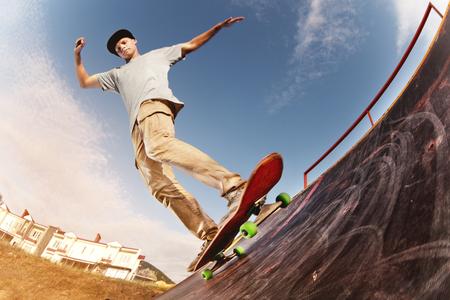Teen skater hang up over a ramp on a skateboard in a skate park