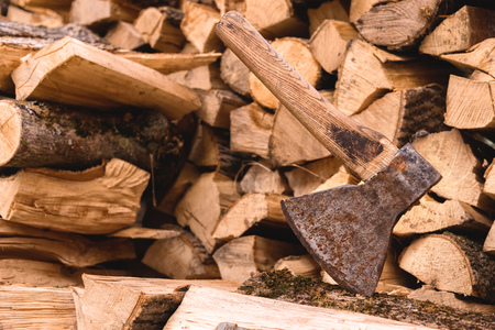 The ax is stuck in a log against the backdrop of chopped firewood lying in a flat pile Stock Photo