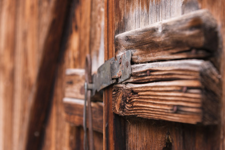 old simple lock on a wooden door closed with a metal pin rustic latch on an old door made of wood Stock Photo