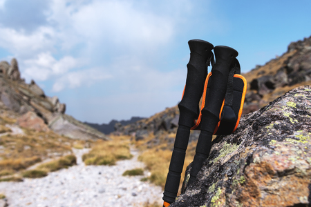 Professional sticks for climbing a mountain near a stone on a high mountain path against a blue sky and white clouds.
