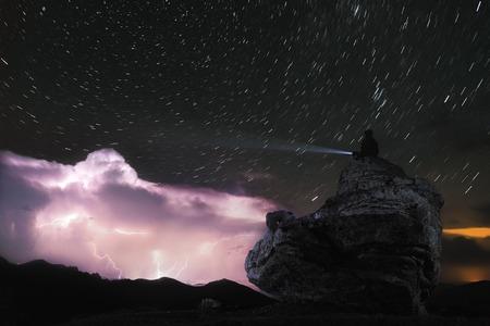 Foto nocturna Un hombre se sienta en una roca y brilla una linterna en el cielo en la que relámpagos destellan en las nubes en el cielo estrellado Foto de archivo