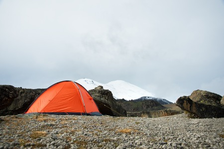 An orange high-altitude tent is set high in the mountains against the background of the Caucasian ridge