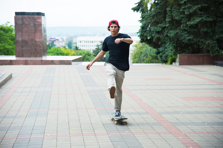 A guy in a cap accelerates pushing his foot on his skateboard Banco de Imagens